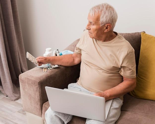 Mittlerer schuss alter mann, der pillen hält
