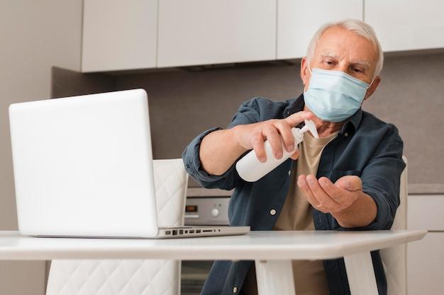 Mittlerer schuss alter mann mit desinfektionsmittel