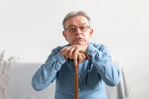 Mittlerer schuss alter mann mit stock