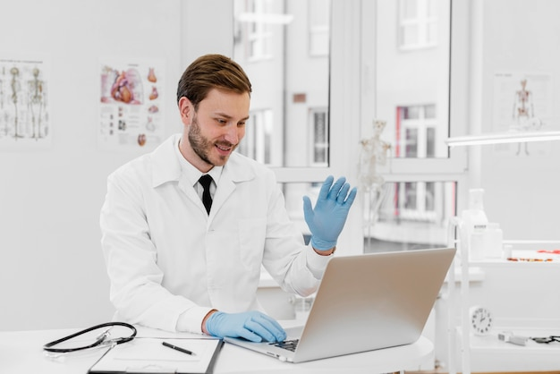 Mittlerer schuss arzt, der am laptop arbeitet