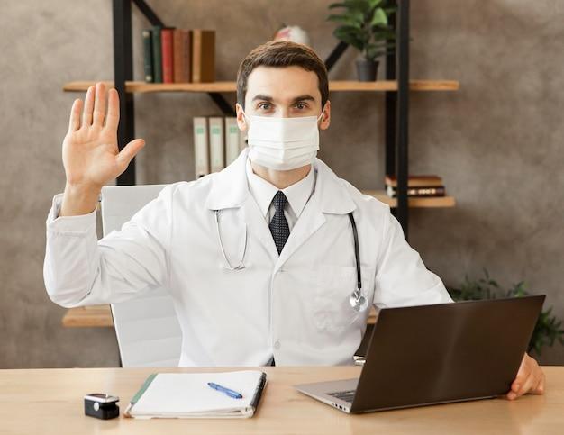 Mittlerer schuss arzt, der medizinische maske trägt