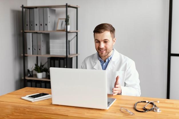 Mittlerer schuss arzt, der mit laptop arbeitet
