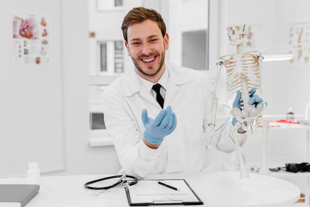 Mittlerer schuss arzt hält skelett