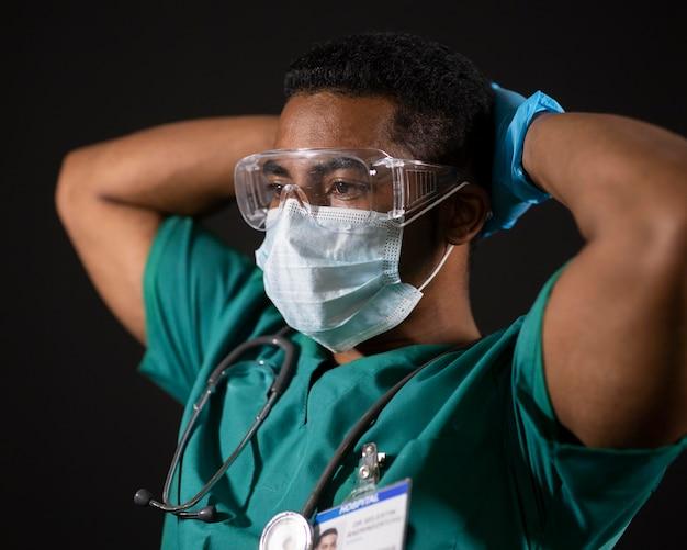 Mittlerer schuss arzt mit schutzbrille und maske