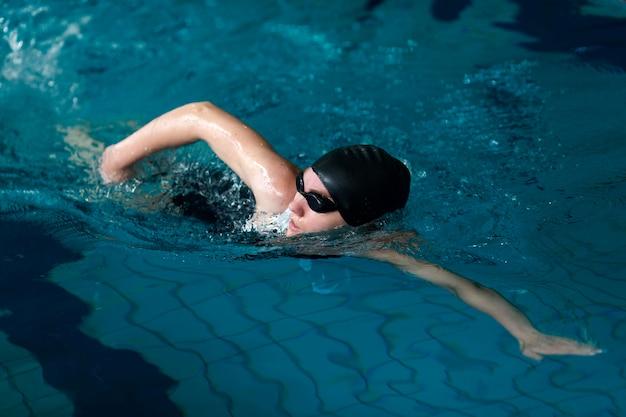 Mittlerer schuss athlet, der im pool schwimmt