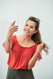 Mittlerer schuss attraktiver dame, die ein selfie mit einem smartphone nimmt