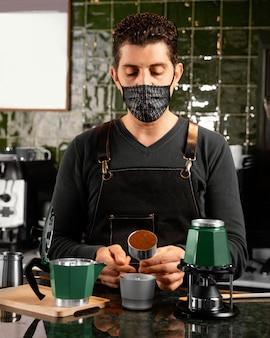 Mittlerer schuss barista, der kaffee vorbereitet