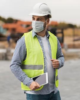 Mittlerer schuss baumeister mann, der medizinische maske trägt