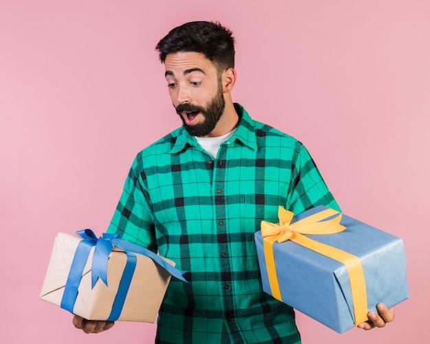 Mittlerer schuss begeisterter kerl, der geschenke hält