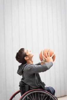 Mittlerer schuss behinderter mann, der basketball spielt