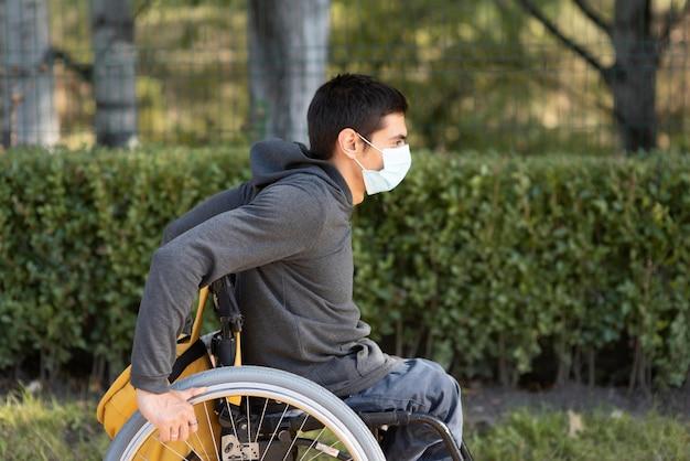 Mittlerer schuss behinderter mann, der maske trägt