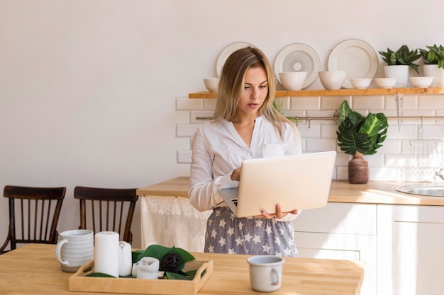 Mittlerer schuss beschäftigte frau, die laptop hält