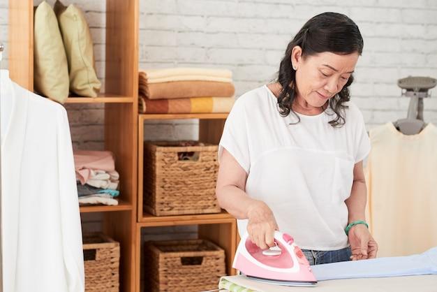 Mittlerer schuss bügelnden leinens asiatischer dame an einem wäschereitag