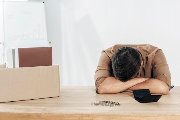 Mittlerer schuss depressiver mann am tisch