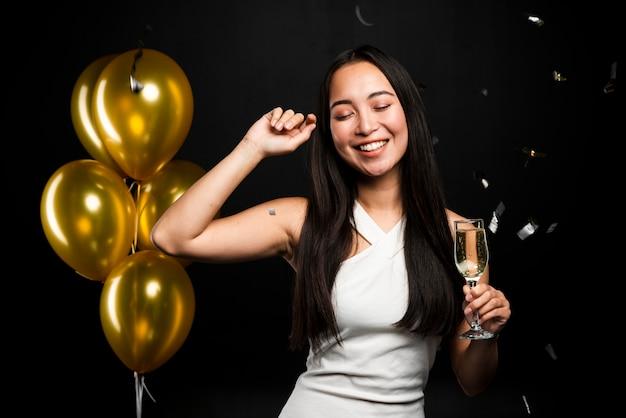 Mittlerer schuss der eleganten frau aufwerfend an der party