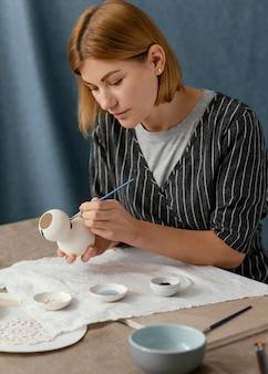 Mittlerer schuss der frau, die keramikgegenstand malt