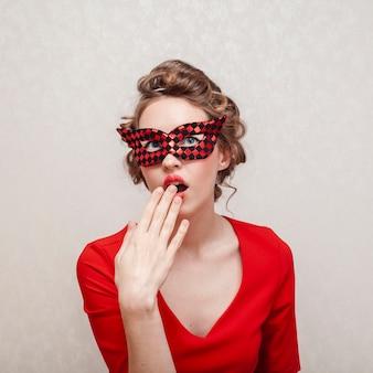 Mittlerer schuss der frau ihr gesicht mit karnevalsmaske bedeckend
