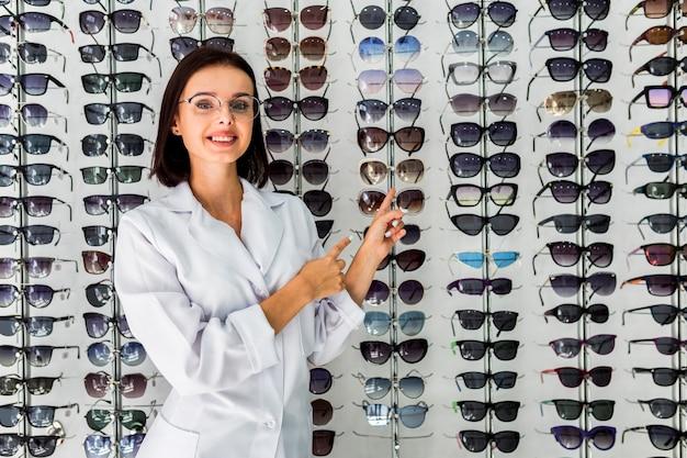 Mittlerer schuss der frau mit sonnenbrillebildschirmanzeige