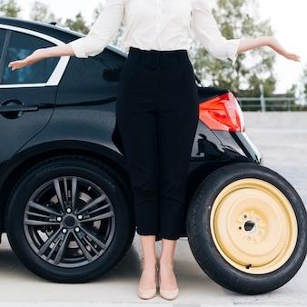 Mittlerer schuss der frau und des schwarzen autos
