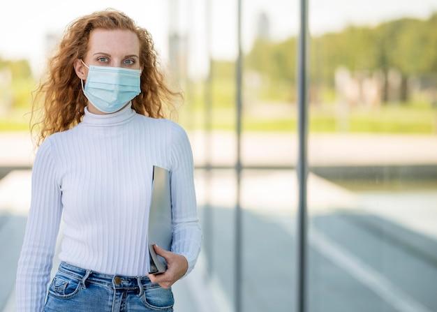 Mittlerer schuss der geschäftsfrau, die medizinische maske trägt