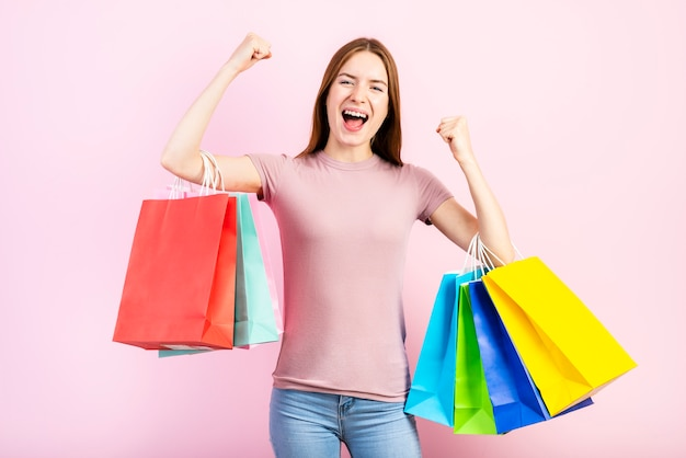 Mittlerer schuss der glücklichen frau einkaufstaschen halten