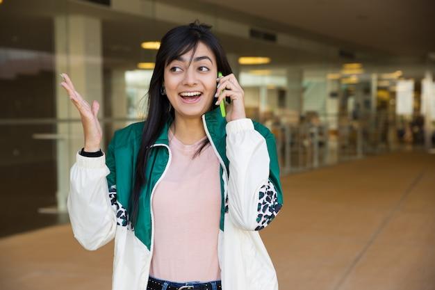 Mittlerer schuss der hübschen frau sprechend am telefon, schauend überrascht
