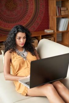 Mittlerer schuss der jungen frau zu hause arbeitend an laptop