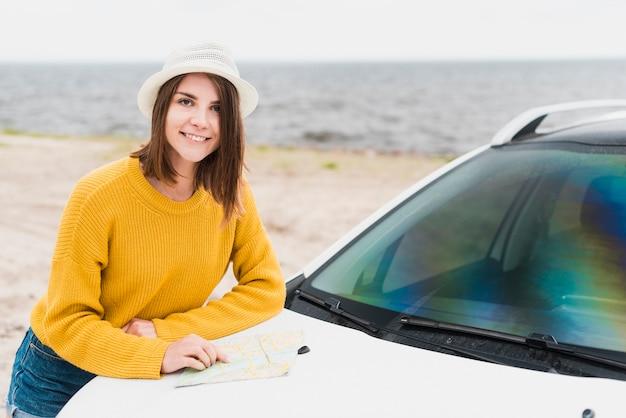 Mittlerer schuss der reisenden frau und des autos