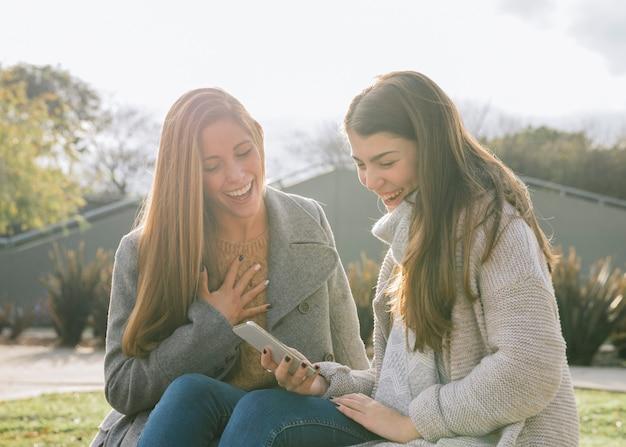 Mittlerer schuss der seitenansicht von zwei jungen frauen, die das telefon im park betrachten