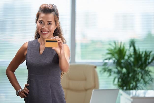 Mittlerer schuss der überzeugten frau stehend im büro und eine kreditkarte zeigend