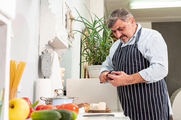 Mittlerer schuss des älteren mannes, der kocht