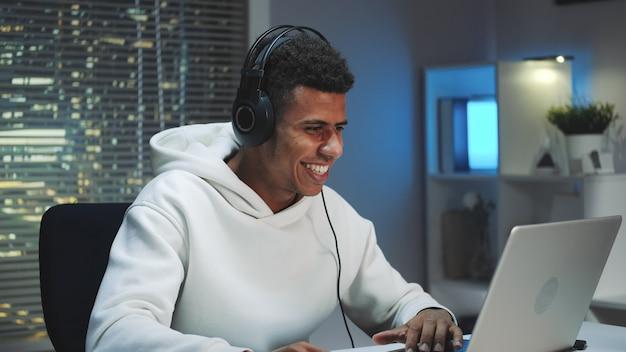 Mittlerer schuss des afrikanischen spielers in den kopfhörern, die online-spiel auf computer gewinnen
