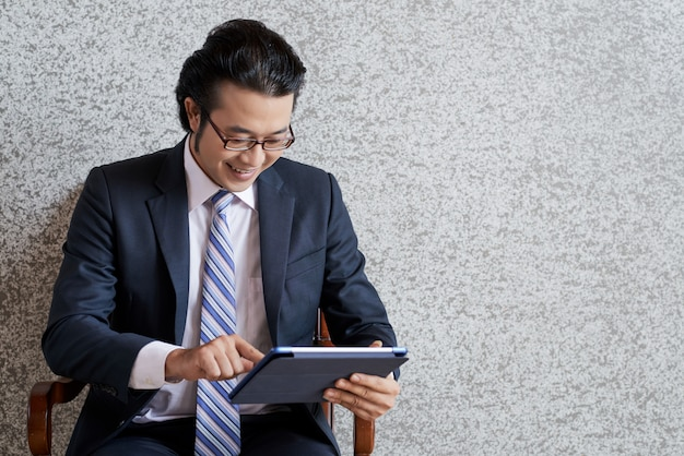 Mittlerer schuss des asiatischen geschäftsmannes, der die digitale auflage verwendet