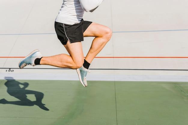 Mittlerer schuss des athleten springend während seines trainings