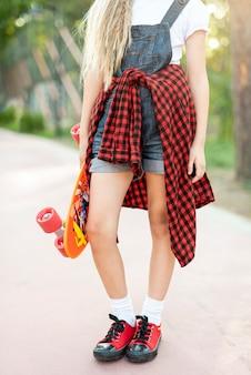 Mittlerer schuss des blonden mädchens mit skateboard