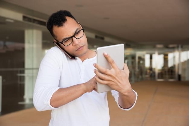 Mittlerer schuss des ernsten mannes arbeitend an der tablette, sprechend am telefon