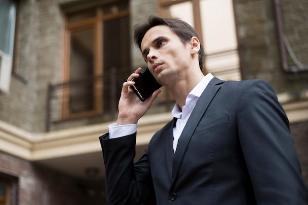 Mittlerer schuss des geschäftsmannes sprechend am telefon