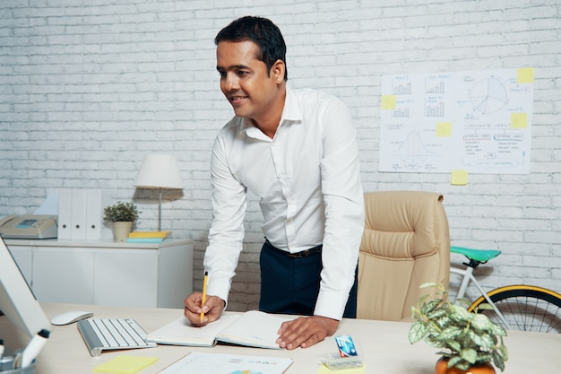 Mittlerer schuss des hübschen indischen geschäftsmannes, der an seinem schreibtisch im büro steht