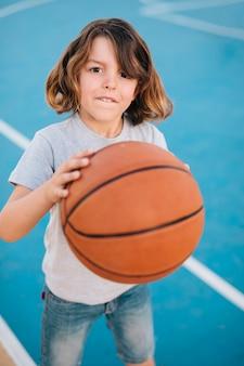 Mittlerer schuss des jungen basketball spielend