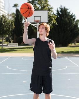 Mittlerer schuss des jungen, der mit basketballball spielt