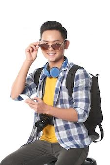Mittlerer schuss des jungen jugendlichen asiatischen kerls, der auf seinem gepäck sitzt und seine sonnenbrille entfernt