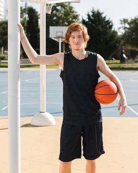 Mittlerer schuss des jungen mit basketballball