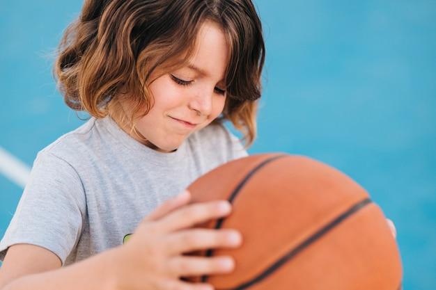 Mittlerer schuss des kindes basketball spielend