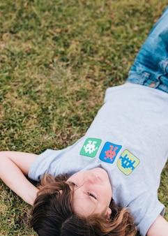 Mittlerer schuss des kindes liegend auf gras
