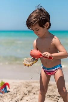 Mittlerer schuss des kindes spielend mit sand am strand