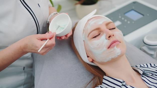 Mittlerer schuss des kosmetikers, der crememaske auf gesicht der frau am schönheitssalon setzt