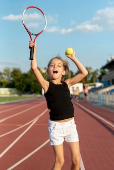 Mittlerer schuss des mädchens tennis spielend