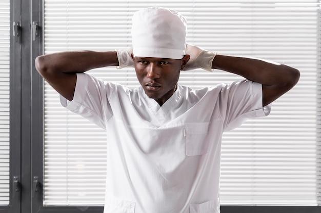 Mittlerer schuss des männlichen arztes, der weiße kleidung trägt