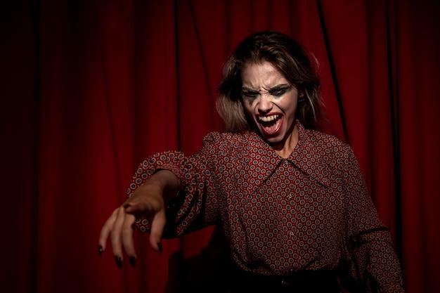 Mittlerer schuss des make-upfrauenclowns zeigend mit ihrem finger