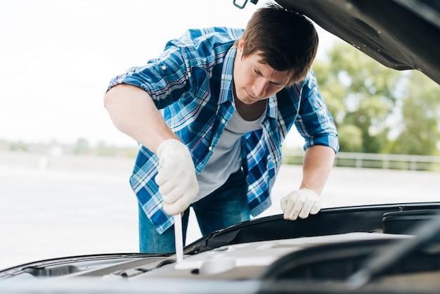 Mittlerer schuss des mannes arbeitend an auto